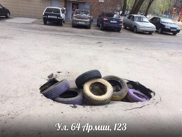 Гигантскую яму на юге Волгограда дорожники прикрыли шинами с детской площадки